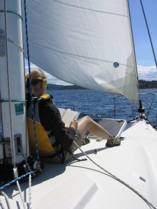 Person leaning against the mast on a sailboat - Sailing Lessons - Bareboat Charter