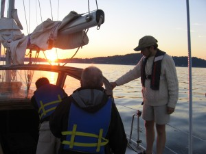 Sailors on a boat with a sunset - Basic Coastal Cruising Sailing Lesson